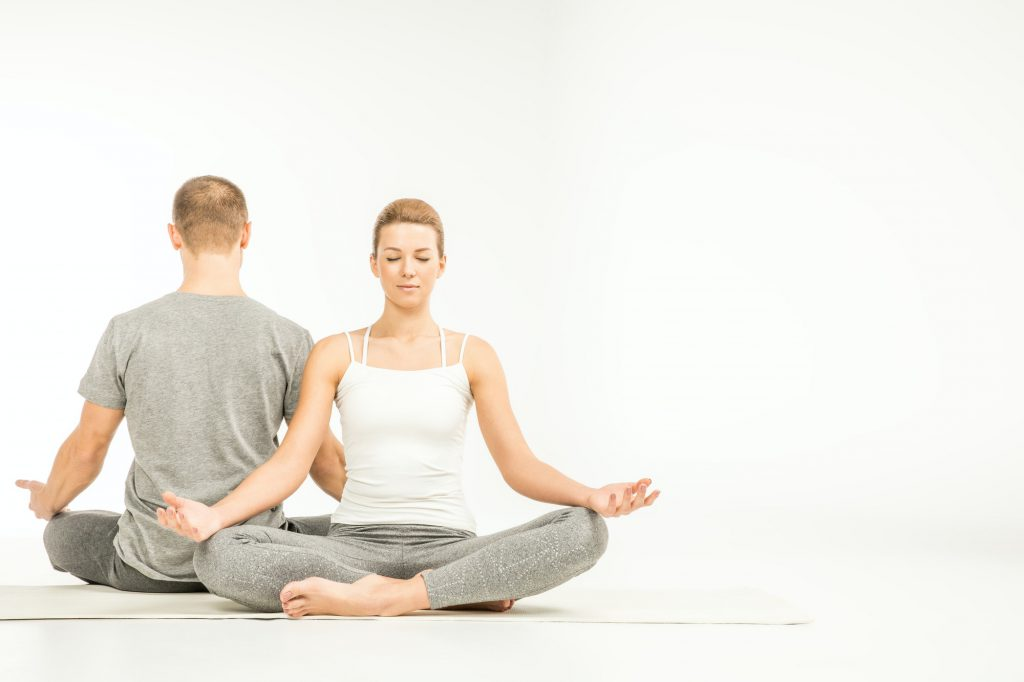 Young couple practicing yoga sitting in lotus position on yoga mats isolated on white